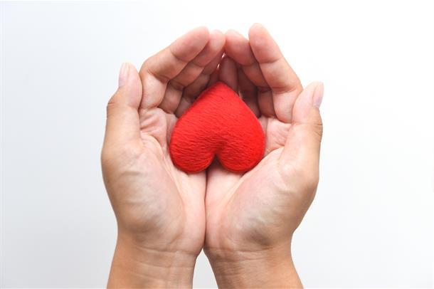 Rødt tøyhjerte som ligger i en hånd som strekkes fram